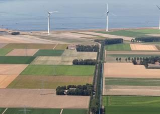 Aerial view Dutch agricultural landscape with wind turbines along coast by iStock/kruwt